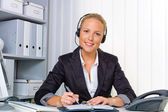 Friendly woman with a headset in customer service — Stock Photo