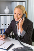 Woman with a telephone in the office — Stock Photo