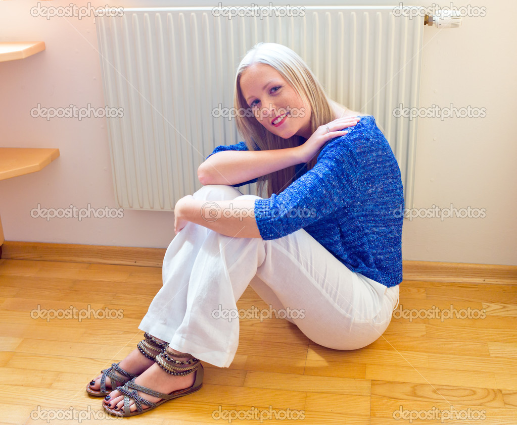 A young woman sits in front of a radiator in the winter. — Stock Photo #11888431