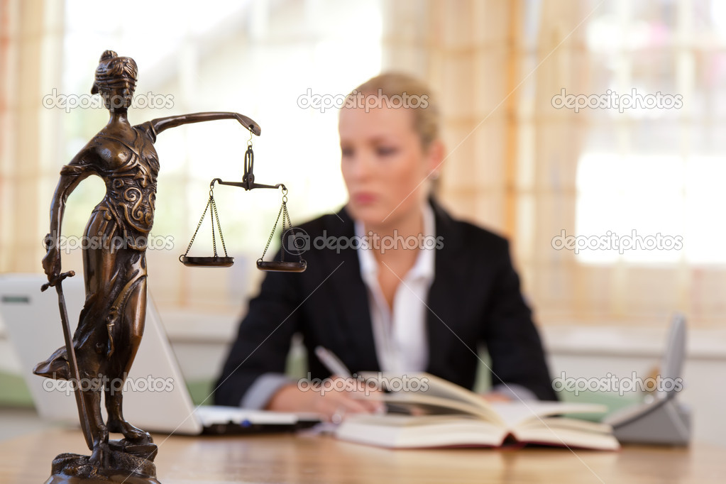 A young lawyer is sitting at her desk in the office  Stock Photo #11888558