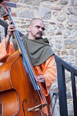 Medieval musician playing the double bass — Stock Photo