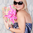 Cheerful young blond girl with a present — Stok fotoğraf