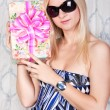 Pretty blond girl with a present — Stock Photo