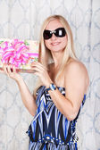 Joyful young blond girl with a present — Stock Photo