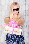 Attractive young blond girl with a present — Photo