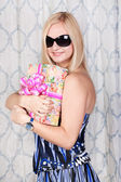 Smiling young lady with a present — Stock Photo