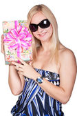 Cute smiling girl holding a present — Stock Photo