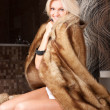 Sexy smiling blond girl with fur — Stock Photo