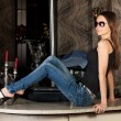 Gorgeous brunette in a stylish jeans on a bar table — Stock Photo