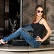 Seductive brunette in a stylish jeans on a bar table — Stock Photo