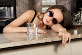 Hot brunette with a glass in a bar — Stock Photo