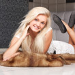 Stock Photo: Lovely blond model in dress on fur