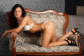 Gorgeous brunette lady in white lingerie on a vintage sofa — Stock Photo