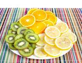 Owoce tropikalne na tabliczce na kolorowe tło — Zdjęcie stockowe