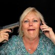 Stock Photo: Mature Blonde Womwith Cell Phone and Handgun (3)