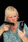 Mature Blonde Woman with Cell Phone and a Handgun (1) — Stock Photo