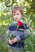 Sad little boy holding red rose in her hand, park — Stock Photo