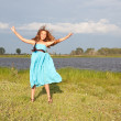 Funny little girl jumping on green field, summer — Stock Photo