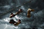 Scarpe da ginnastica appeso su una linea telefonica — Foto Stock