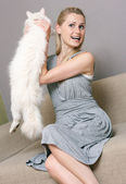 Happy woman holding cat while sitting in couch — Stock Photo