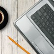 Laptop and coffee cup on wooden table — Stock Photo