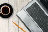 Laptop and coffee cup on wooden table — Stock fotografie