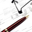 Pen and glasses on financial report — Stockfoto