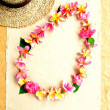 Lady's straw hat with pink plumeria lei — Stock Photo