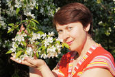 Woman and blossoming branch of the apple tree — Stock Photo