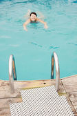 Swimming woman in an outdoor pool (focus on foreground) — Stock Photo