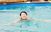 Woman is swimming in an outdoor pool — Stock Photo