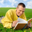 Royalty-Free Stock Photo: Man on a meadow reading cheerfully