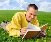 Man on a meadow reading cheerfully — Stock Photo