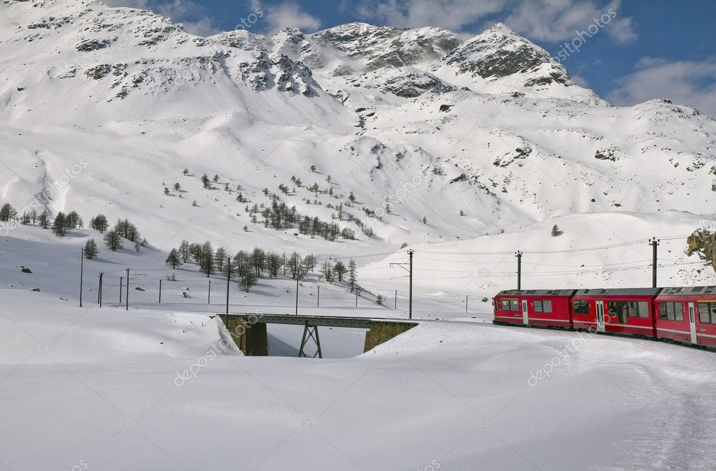 Red train in snow valley among alpine peaks — Stock Photo #10834110