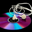 Stock Photo: Earphones lying on compact disc