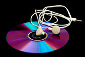 Earphones lying on a compact disc — Stock Photo
