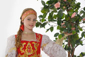 Russian girl in national dress next to a blossoming tree — Stock Photo