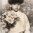Little boy wearing a cap with flowers in their hands — Stock Photo #11040190