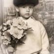Little boy wearing a cap with flowers in their hands - Stock Photo