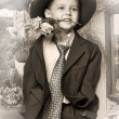 Little boy wearing a cap with flowers in their hands - Foto Stock