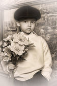 Little boy wearing a cap with flowers in their hands — Stock Photo