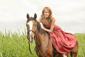 Woman in red dress on a horse — Stock Photo
