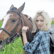 Sexy blonde beside the horse — Stock Photo