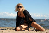 Sexy blonde in black on the beach — Stock Photo