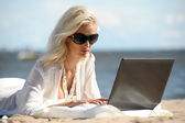 Happy blonde woman at a beach with a laptop — Stock Photo