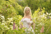 Girl in a white dress in the field among the flowers — Stock Photo