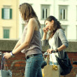 Foto Stock: Two Girls While they make shopping in bicycle to Pisa