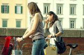Deux filles alors qu'ils font shopping à bicyclette à pise — Photo