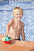 Boy with watering can in the swimming pool — Stock Photo