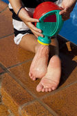 Child´s legs with watering can on the swimming pool background — Stock Photo